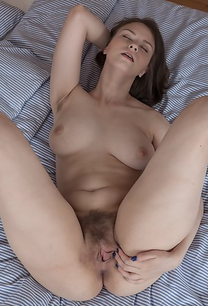 Beata is on her bed, in her blue bra and black stockings. She strips and shows her hairy pits and looks sexy. She finishes getting naked, and touches her hairy pussy all over and much more.
