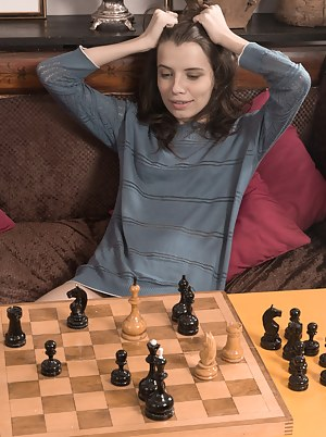 Christy is finishing a game of chess and after losing has to strip naked. She gets nude, and then lays across the table. She uses the chess pieces across her naked body and across her hairy pussy.