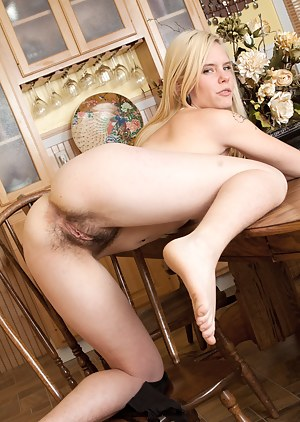 While lifting her dress, Usnea bends her sexy hairy ass over the table. The thought of being taken from behind excites her enough to play in the nude.