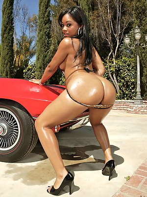 Awesome ebony lady is taking off her clothes next to the cool red car outdoor. She is also having wild interracial sex with man having big cock.